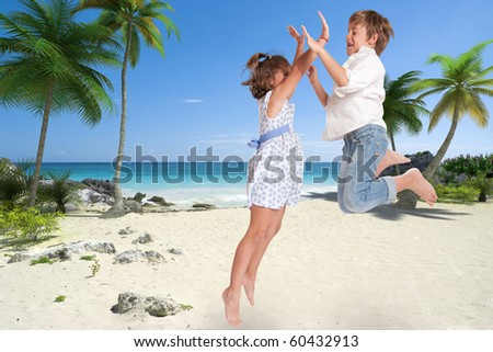 Little boy and girl happily jumping on a tropical beach - stock photo