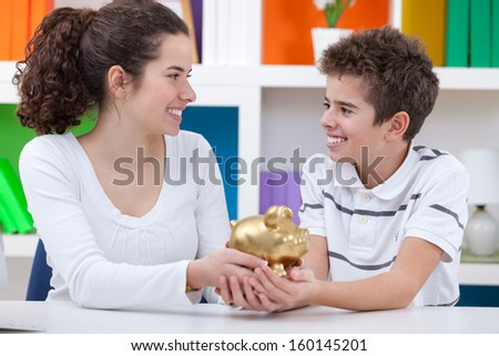 Little boy and girl happy saving money in pink piggy bank - stock photo