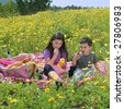 little boy and girl having a picnic in a yellow flowers field - stock photo