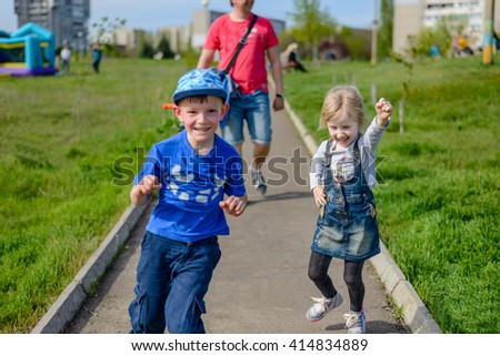 Little boy and girl having fun outdoors laughing and jumping as they run along a path followed by their father in the background - stock photo