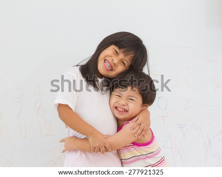 little boy and girl hugging and smiling on wall background - stock photo