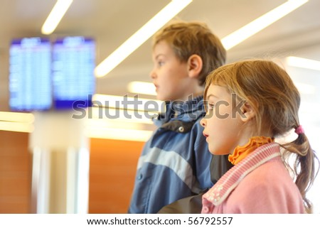 little boy and girl in airport blue screens on background side view half body - stock photo