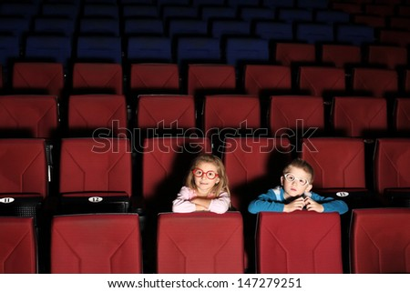 Little boy and girl in an empty cinema hall - stock photo