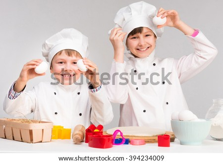 little boy and girl in cook form holding eggs  - stock photo