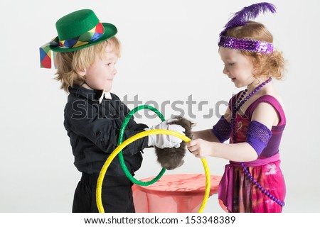 Little boy and girl in costumes of magicians shows trick with a kitten and rings - stock photo