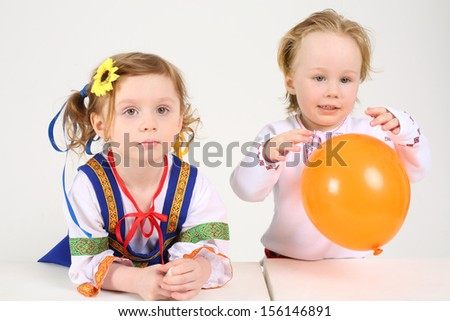 Little boy and girl in folk costumes sit at table and play with balloon on white background.