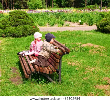 Little boy and girl in park on a bench