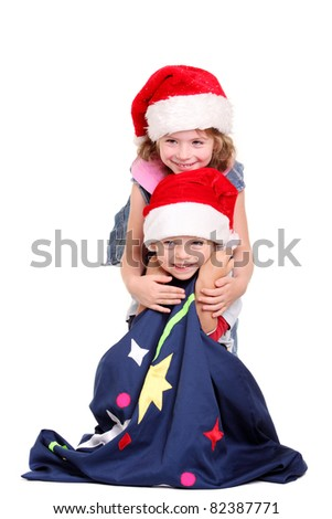 Little boy and girl in Santa Claus hats on white background
