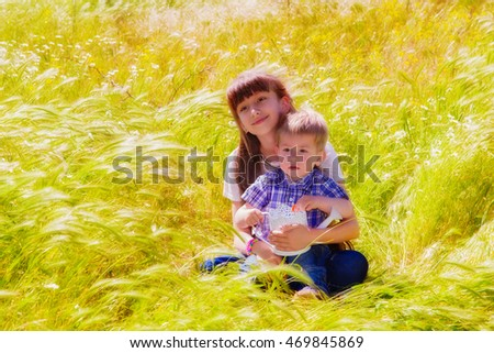 Little boy and girl in the summer field with flowers. The girl's sister and brother hugging little boy