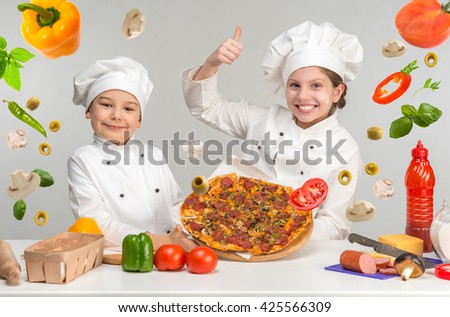 little boy and girl in white uniform of chef by the table with flying pizza