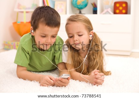 Little boy and girl listening to music together on a portable player, laying on the floor - stock photo