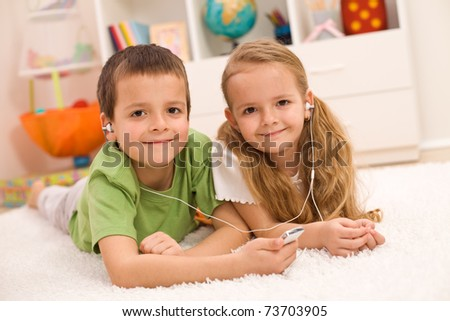 Little boy and girl listening to music together sharing earphones, laying on the floor at home - stock photo