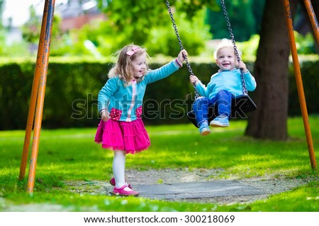 Little boy and girl on a playground. Child playing outdoors in summer. Kids play on school yard. Happy kid in kindergarten or preschool. Children having fun at daycare play ground. Toddler on a swing. - stock photo