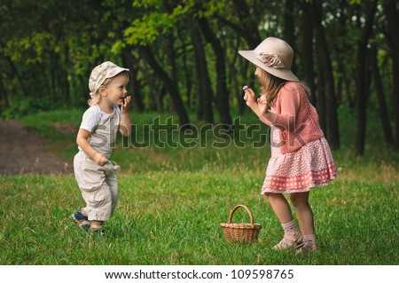 little boy and girl on the grass in the forest - stock photo