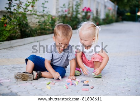 Little boy and girl painting with chalks outdoors - stock photo