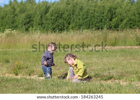 Little boy and girl paly on grass at green meadow in sunny day