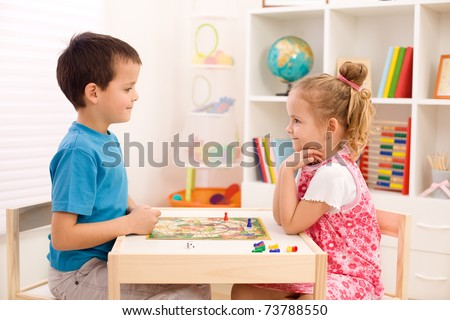 Little boy and girl playing board game in their room sitting at the table - stock photo