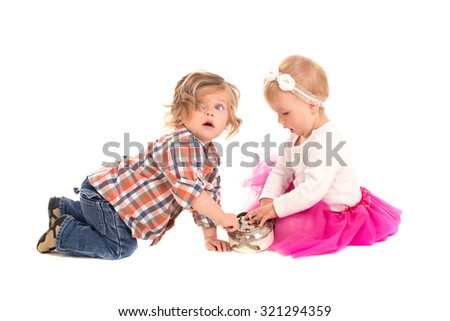 little boy and girl playing with alarm clock isolated on white background - stock photo