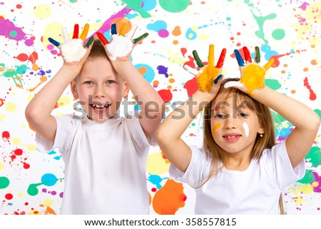 Little boy and girl playing with flowers, a boy and a girl shows painted hands - stock photo