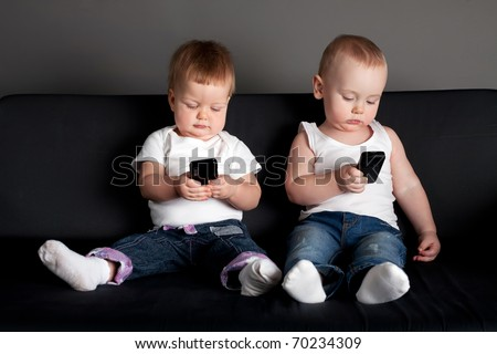 little boy and girl playing with mobile phones - stock photo