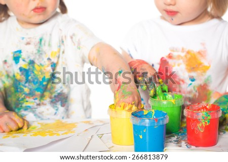 Little boy and girl playing with paints - stock photo