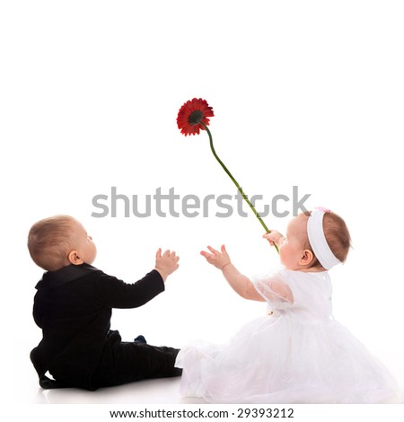 little boy and girl playing with red flower - stock photo