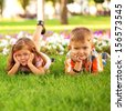 Little boy and girl relaxing on the grass among flowers. - stock photo