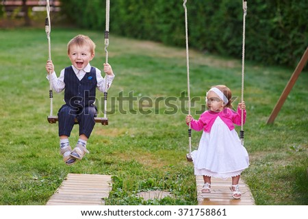 Little boy and girl ride in the park on a swing. - stock photo