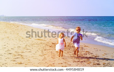 little boy and girl running at beach - stock photo