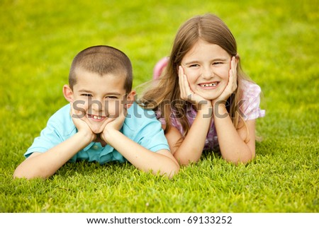 Little boy and girl sitting outside - stock photo