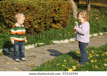 Little boy and girl walk in the park