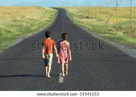 Little boy and girl, walking hand in hand down endless tarred road