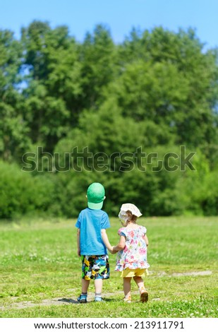 Little boy and girl walking in the park hand in hand - stock photo