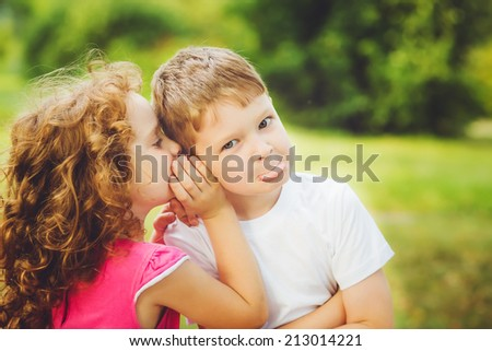 Little boy and girl whispers. - stock photo