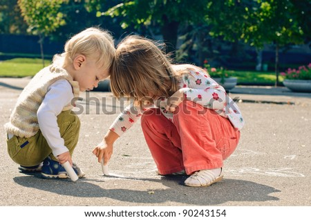little boy and girl with crayons, they drawing on the asphalt - stock photo