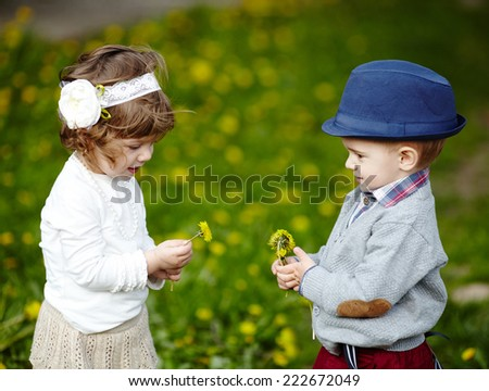 little boy and girl with dandelions - stock photo