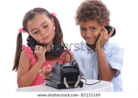 Little boy and girl with old fashioned telephone - stock photo