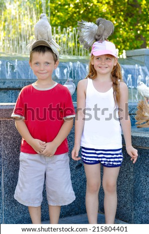 Little boy and girl with pigeons on their heads - stock photo