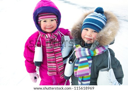 Little boy and girl with  skates  in wintertime backgruond snow - stock photo