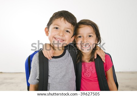 Little boy and girl with their book bags - stock photo