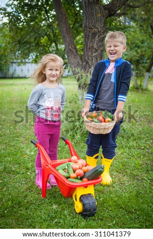 little boy and girl with vegetables in the garden
