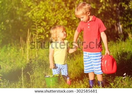 little boy and girl working in the garden, kids harvesting