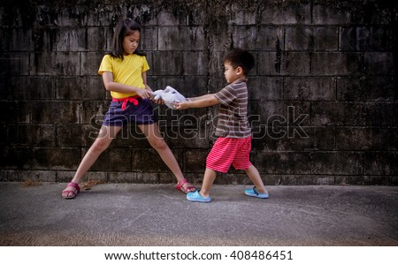 little boy and girls fighting and shared doll - stock photo