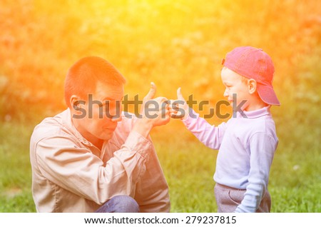 Little boy and his dad playing in the background of the sun. Family composition - stock photo