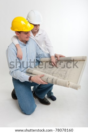 Little boy and his dad with safety helmets consulting a plan - stock photo