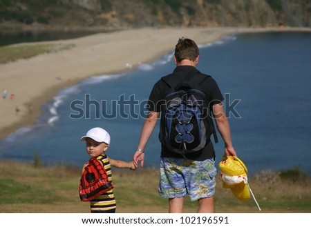 Little boy and his father are going to the beach - stock photo