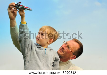 Little boy and his father are playing outdoor - stock photo