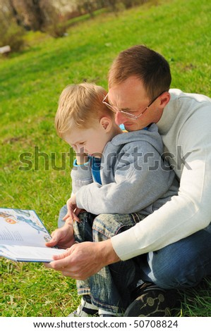 Little boy and his father are reading a book outdoor - stock photo