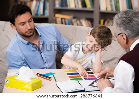 Little boy and his father talking with psychologist. Psychologist making test with boy. Sad boy choosing color cards. There are many books in psychologist office - stock photo