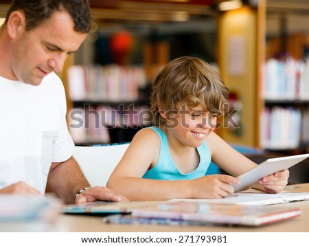 Little boy and his father with computer in library - stock photo
